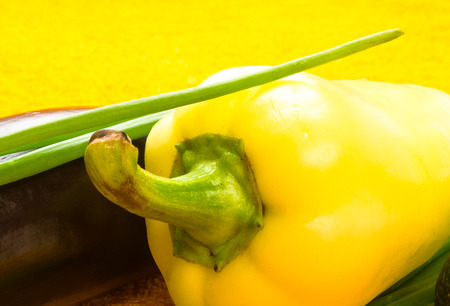 still life - onion, lettuce, cucumber, cilantro, eggplant, zucchini, garlic peas and peppers on a bright yellow background