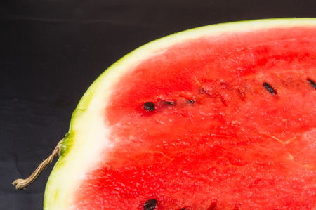 sliced watermelon: half of ripe watermelon on a black background Stock Photo
