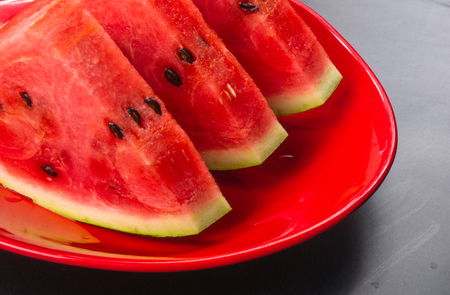 slices of ripe juicy watermelon in red plate on black background