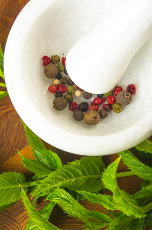 Fresh spearmint herb Mentha in the marble mortar with a pestle with spices, on a wooden background