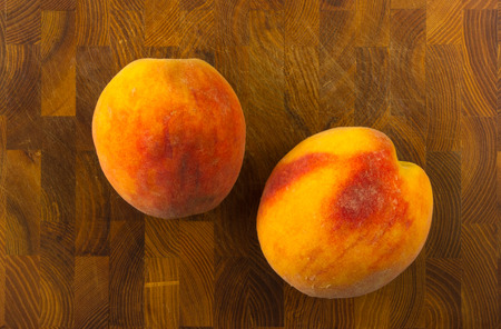 big ripe peaches on a wooden background