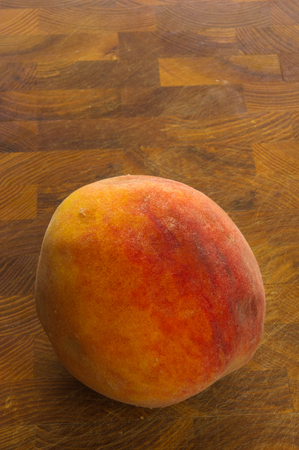 One big ripe peach on a wooden background