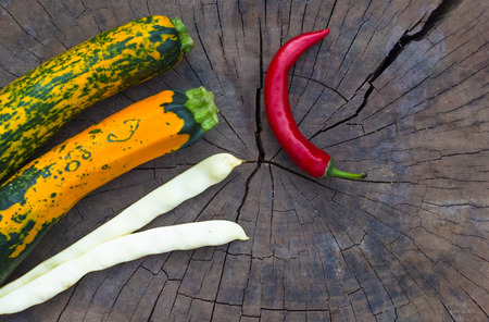chilly: unusual green-orange zucchini, pods of white beans and red chilly on an old wooden background Stock Photo