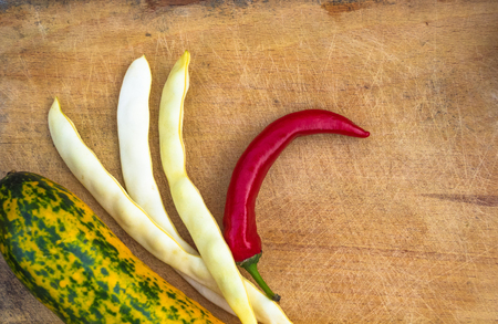 red chilly: unusual green-orange zucchini, pods of white beans and red chilly on an old wooden background Stock Photo