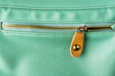 seams: closeup of the fittings and seams on green leather hand bag