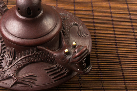 chinese teapot: brown Chinese teapot of Yixing clay with traditional ornament on bamboo Mat