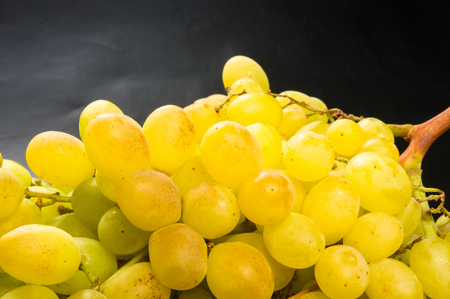 Large grapes cluster amber color on black background Stock Photo