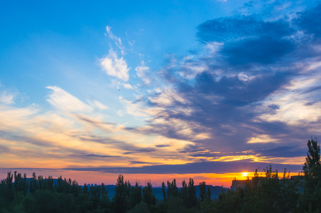 cloudscapes: landscape with dramatic light - orange clouds and the outline of trees at sunrise