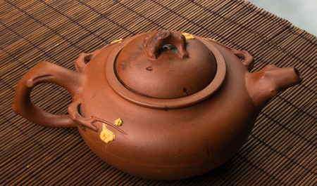 loose leaf: brown Chinese teapot of Yixing clay with traditional ornament on bamboo Mat