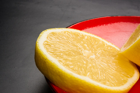 Sliced yellow lemon in red saucer on black background