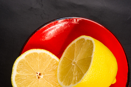ware: Sliced yellow lemon in red saucer on black background