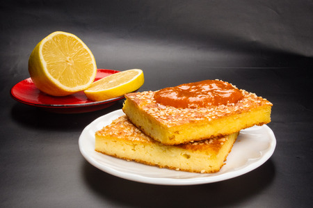 Slice of cheesecake with sesame seeds, apricot jam and lemon slices on a black background Stock Photo