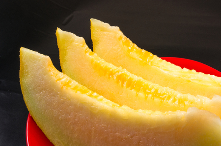 Cantaloupe: slices of ripe juicy melon in red plate on black background