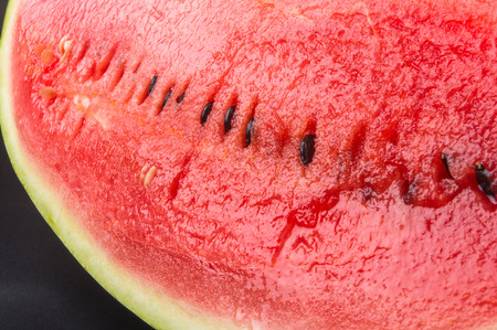 sliced watermelon: a quarter of a ripe watermelon on a black background Stock Photo