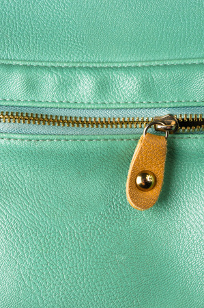 closeup of the fittings and seams on green leather hand bag