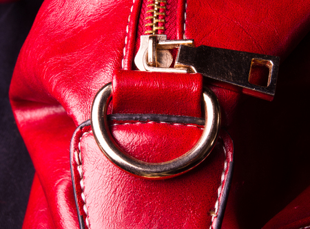 closeup of buckles, clasps, zippers, pockets, fasteners, fittings and seams on red leather hand bag