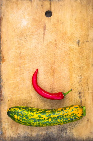 unusual green-orange zucchini and red chilly on an old wooden background Stock Photo