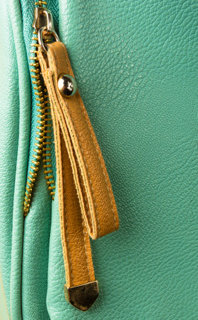 closeup of buckles, clasps, zippers, pockets, fasteners, fittings and seams on green leather hand bag