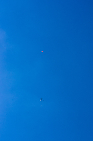 parachutists: dropping parachutists from a helicopter over the sea