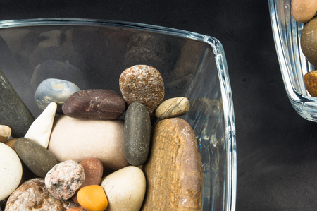 snifter: multicolored decorative pebbles in glass containers on a black background