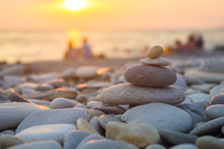 a couple and folded pyramid Zen pebble stones on the sea beach at sunset Stock Photo