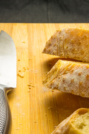 fresh sliced loaf of white wheat bread on wooden background