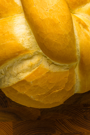 carbohydrates: fresh braided loaf of white wheat bread on wooden background