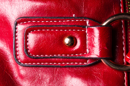 closeup of buckles, clasps, zippers, pockets, fasteners, fittings and seams on the red hand bag Stockfoto