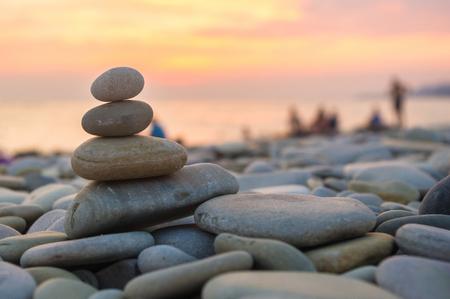 repose: folded pyramid Zen pebble stones on the sea beach at sunset