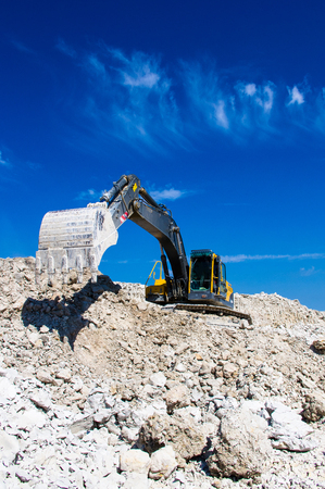 dredging: the excavator digging clay on blue sky background Stock Photo