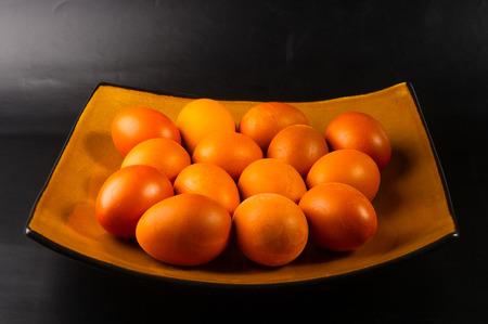 ellipse: huevos coloreados con tinte natural en plato marrón Foto de archivo