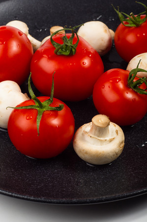 brigh: fresh ripe tomatoes and mushrooms - champignons on black ceramic plate on white background Stock Photo