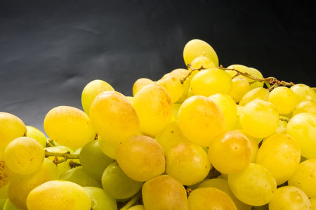 sauvignon blanc: Large grapes cluster amber color on black background Stock Photo