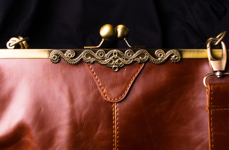 closeup of buckles, clasps, zippers, pockets, fasteners, fittings and seams on brown leather vintage hand bag