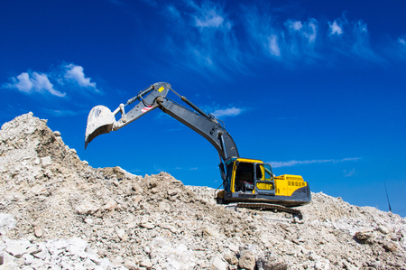 the excavator digging clay on blue sky background Stock Photo