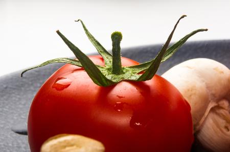 champignons: fresh ripe tomatoes and mushrooms - champignons on black ceramic plate on white background Stock Photo
