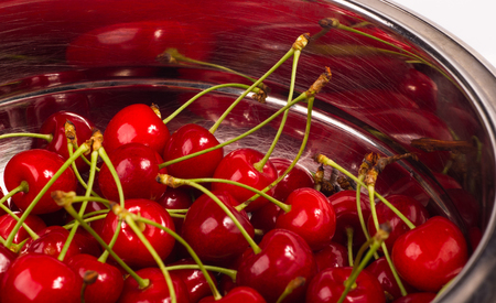 large ripe red cherries in a dish of stainless steel, close-up