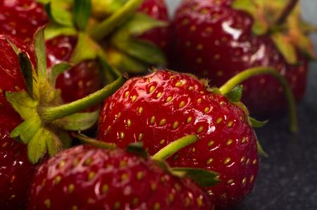 black textured background: fresh ripe berries strawberries on black ceramic plate on white background, macro photo Stock Photo