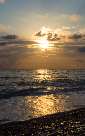Summer sea sunset on the pebble beach, the sun, waves and clouds, beautiful dramatic lighting