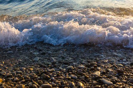 voyage: sea pebble beach with multicoloured stones, transparent waves with foam, on a warm evening