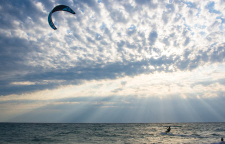 kitesurfer rides a kite-surf on waves of the sea in a small storm on a summer day Stock Photo