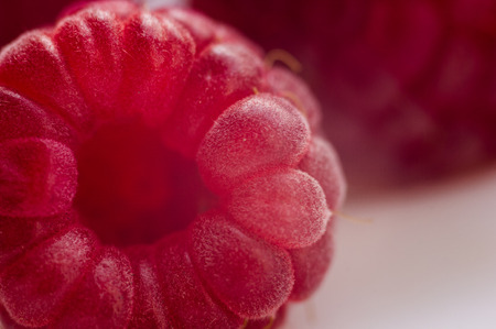 big fresh juicy raspberries on a white saucer close up, macro photo, selected focus