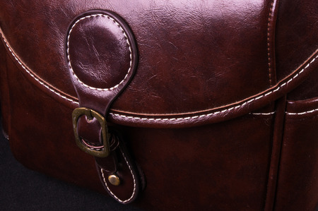 closeup of buckles, clasps, zippers, pockets, fasteners, fittings and seams on the brown retro hand bag