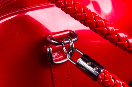 closeup of buckles, clasps, zippers, pockets, fasteners, fittings and seams on the red lacquer hand bag Stock Photo