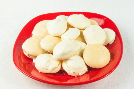 red plate with meringues on a white background