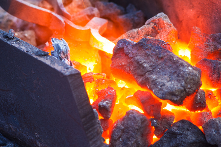 blacksmith furnace with burning coals, tools, and glowing hot metal workpieces, close-up Stock Photo