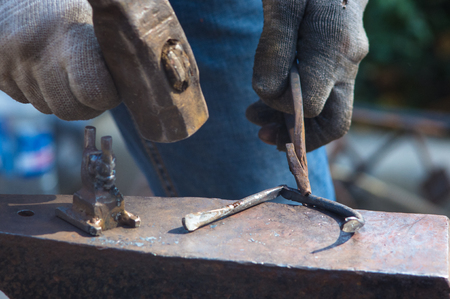 blacksmith performs the forging of hot glowing metal on the anvil, close-up Stock Photo