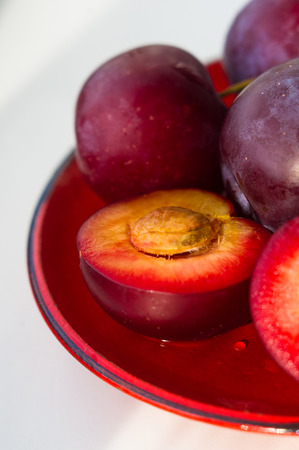 fresh plum fruit with cut plum slices in the red saucer on white background Stock Photo