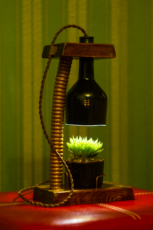 Light fixture handmade - stand for flower pot in vintage style, wooden case, copper fittings, led lamp on a black background.