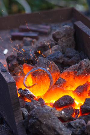 blacksmith furnace with burning coals, tools, and glowing hot metal workpieces Archivio Fotografico